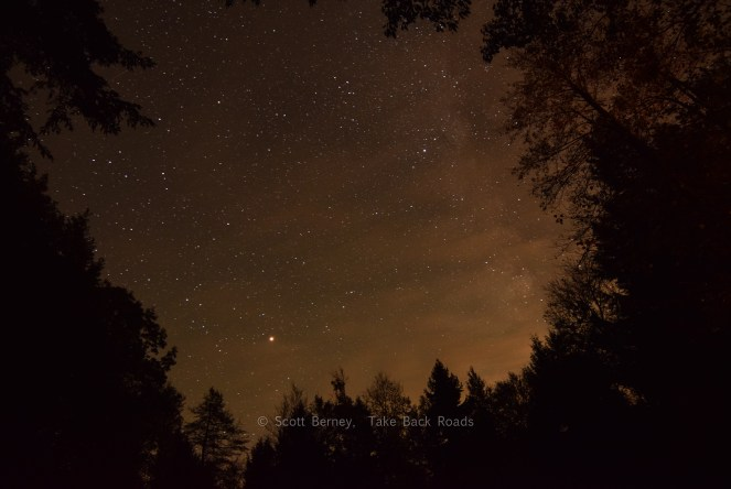 cloudy sky photo. night sky photo. Dark silhouettes of heavy woods frames a starry night sky and the Milky Way, shrouded by a thin wisp of clouds. Milky Way Photography Equipment.