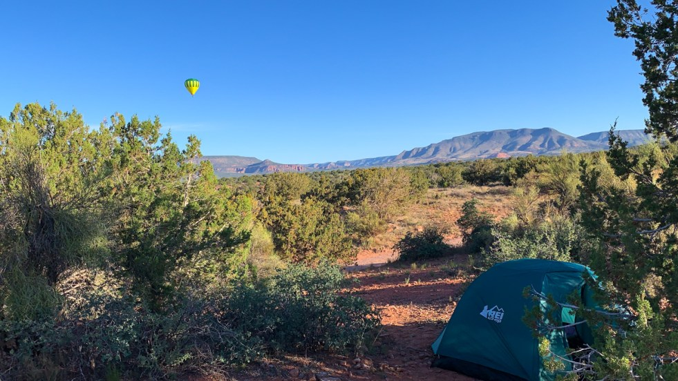 A green REI tent in a wild campsite is tucked up into an evergreen shrub in the Arizona wilderness. Brick red dirt, bright green shrubs, distant mountains and a bright yellow hot air balloon round out the scene.