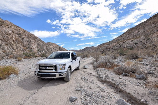 A white Ford F150 pauses on a sandy trail in a desert valley, situated under a perfect blue sky with white clouds.