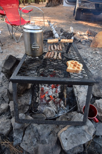 A hearty breakfast of sausage, texas toast, and a large percolator of coffee all cook on a grill over wood coals.