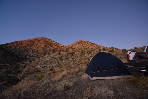 The tops of brush covered hills over a wild campsite start to glow with the first light of sunrise in the Mojave Desert. A tent and open truck bed sit in the foreground.