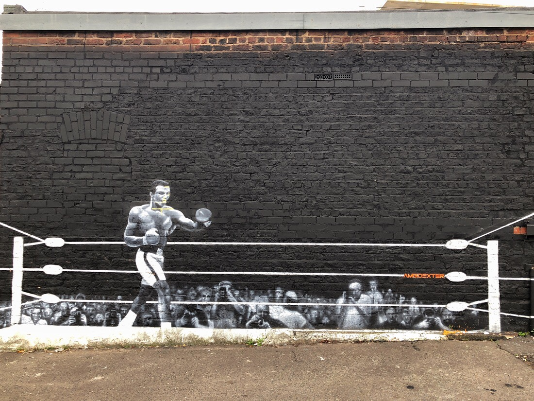 Street art mural of Muhammad Ali on brick street in the Baltic triangle in Liverpool