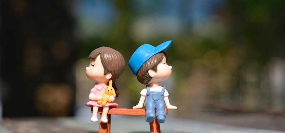 Boy and girl figurine sitting on a bench first date