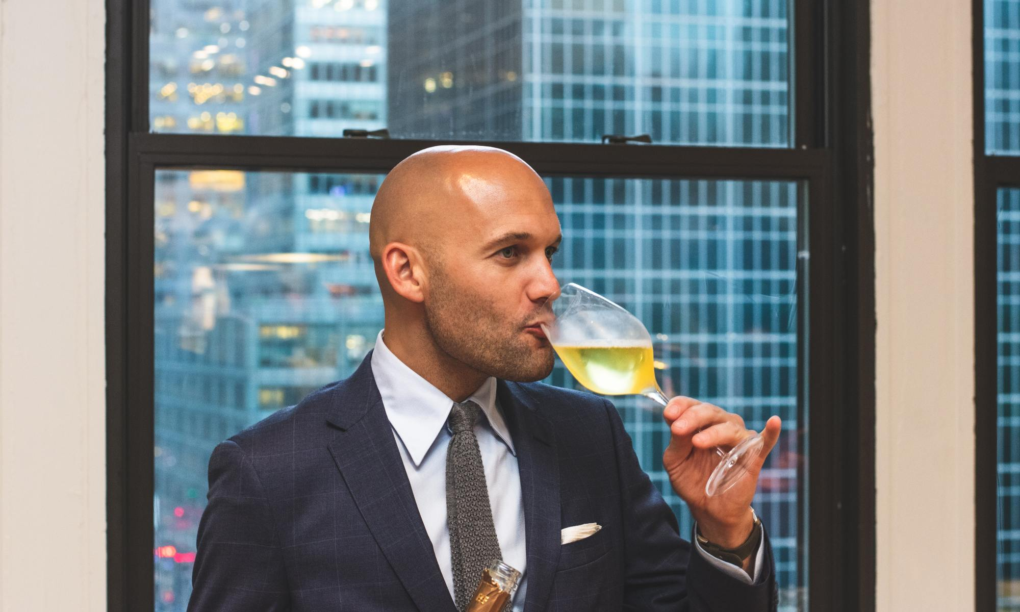 confident man drinking white wine