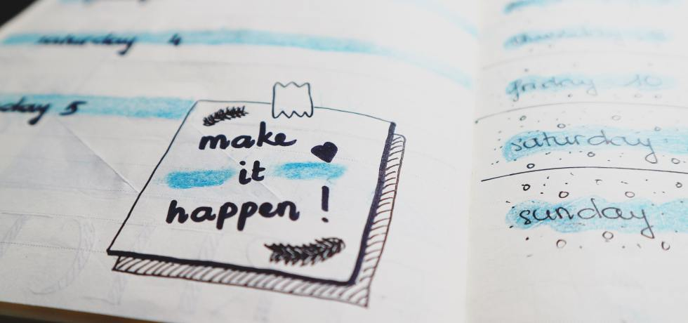 "Piece of paper with ""make it happen"" written on it, for New Year's resolutions"