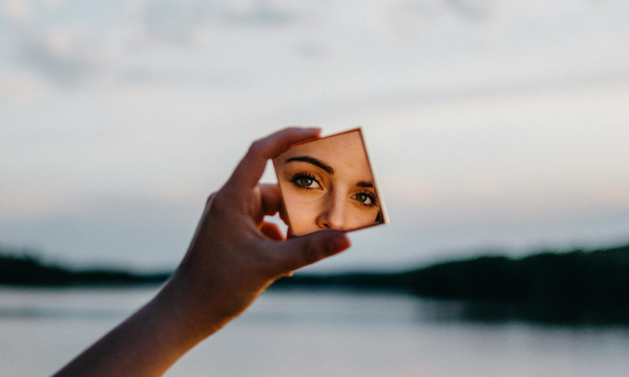 Woman looking at herself in a hand mirror