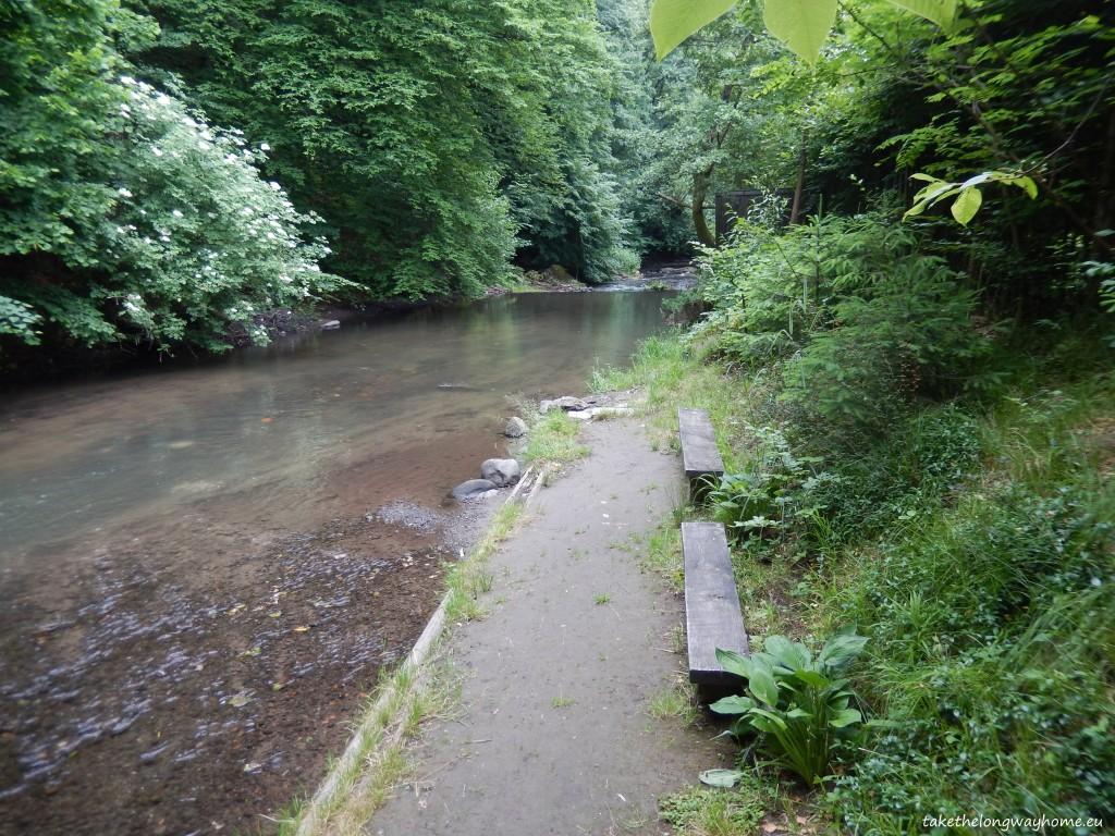 Băncuțe amenajate pe malul râului ce curge prin spatele campingului