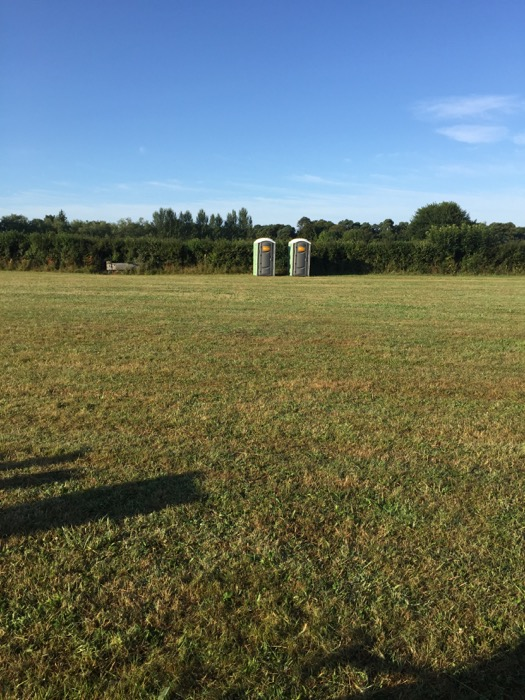 Portaloos on the opposite side of the field to the tent