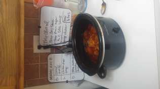 Photo: Slow Cooker BBQ Chicken in crockpot, finished, with a whiteboard in the background listing the ingredients/instructions