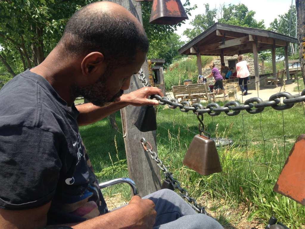 Photo: Calvin feeling the a rail made of chain at a local petting farm