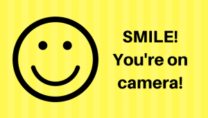 "Graphic: Smiley face to left, text to right says, ""Smile, you're on camera!"""
