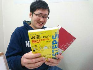 小阪先生の本2冊を眺める多比羅さん