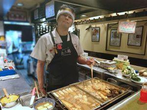 関東煮鍋の前に立つ たこ梅北店の安藤店長