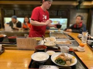 つぎつぎに通る関東煮定食をよそう東店の北川さん