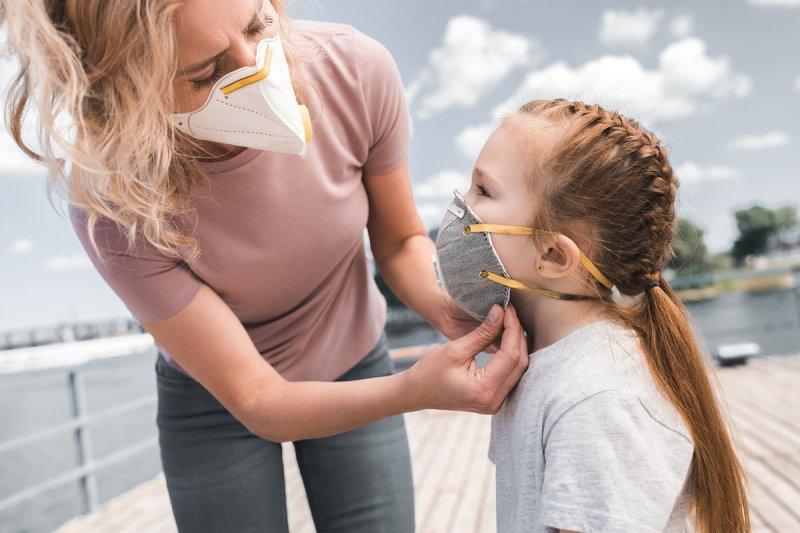 мама надевает дочку маску