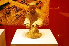 Statueta reprezentand un muzician in genunchi Dinastia Han - 206 i.Ch. - 220 d.Ch. Obiect funerar din argila cenusie pictata.
