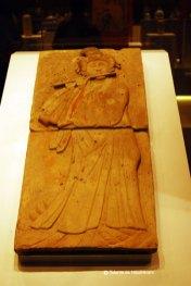 """Femeie care canta la flaut. Perioada celor \""""Cinci dinastii si zece regate\"""", 907-960. Este unul din cei 28 de muzicieni cantand, parte a unui basorelief pictat ce decora un mormant din dinastia Tang."""