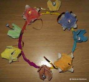 Elise N., Gura Humorului Coroana cu gobluri si clopotei. Materiale: cabluri, hartie creponata, carton oua, folie de aluminiu, acuarele. Ajutor de la mama: lipit cu scoch hartia crep pe cablu (coroana), taiat si gaurit carton.