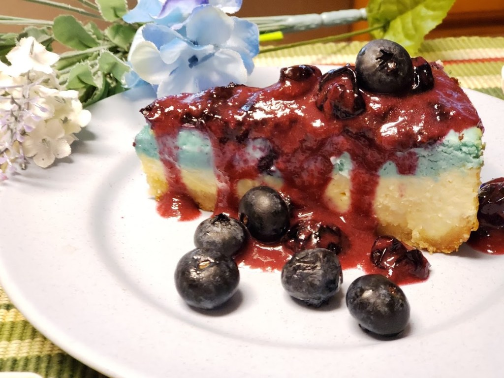 Keto blueberry cheesecake on a plate with flowers.
