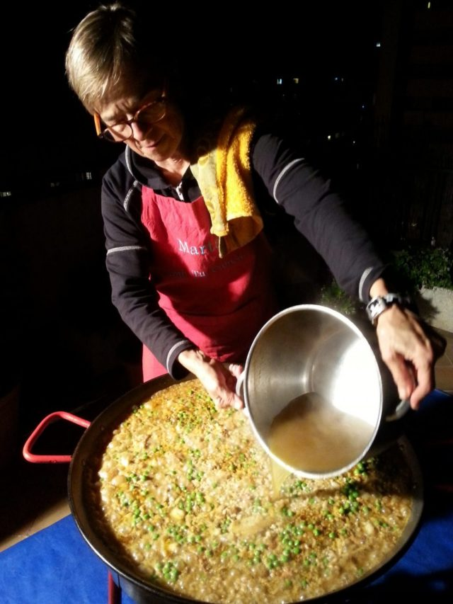 Paella Cooking Class in Barcelona Spain - Marta pours in the stock in the paella pan