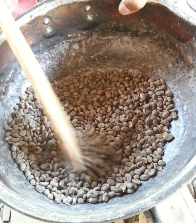coffee beans are roasted over the hob, being stirred constantly