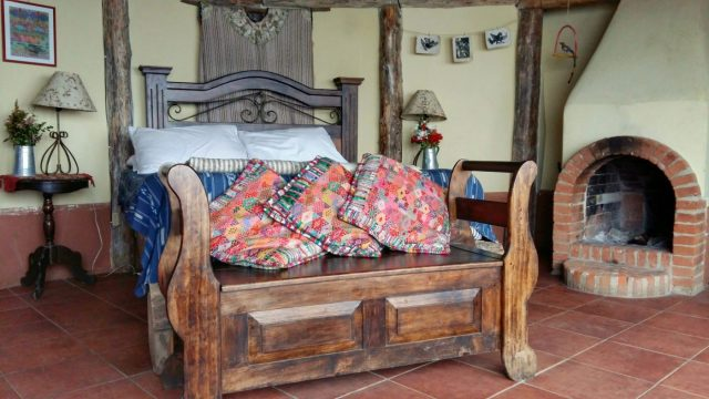 The charming rustic bedroom, and open fireplace in my Hobbit Hole in Hobbitenango guatemala