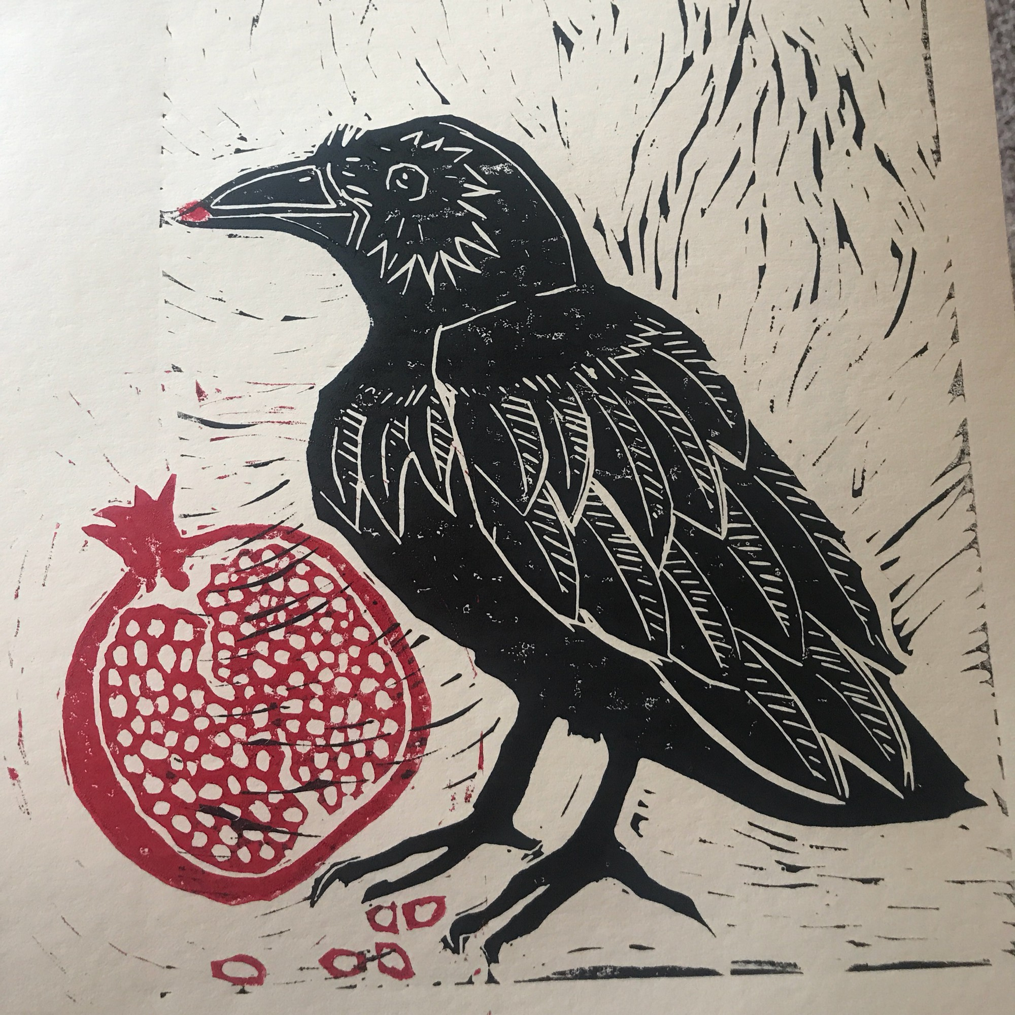 A crow sits near a large pomegranate, there are 5 seeds on the ground, and one it her mouth.