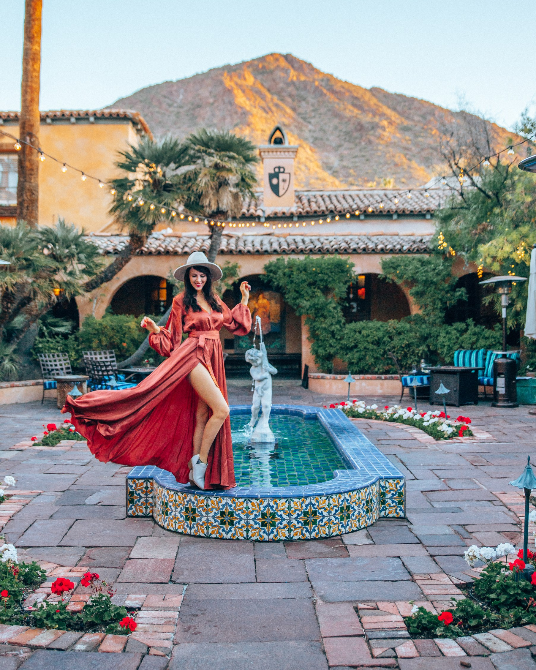 Woman flicking a dress at the main courtyard with a beautiful fountain and the Camelback mountain view