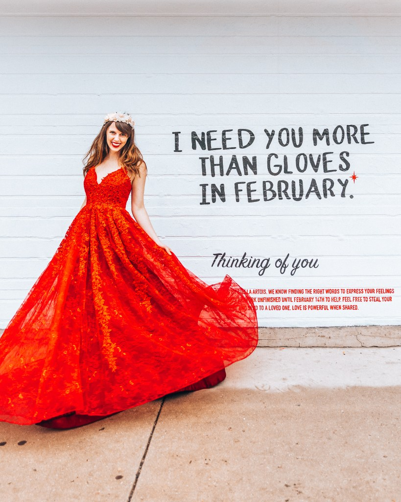 "Woman in a red gown in front of a mural saying ""i need you more than gloves in february""."