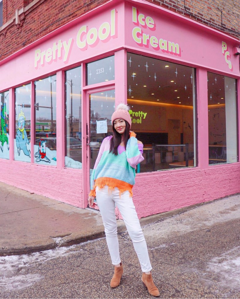 Woman in a pink beanie and colorful sweater in front of a pink ice cream store.
