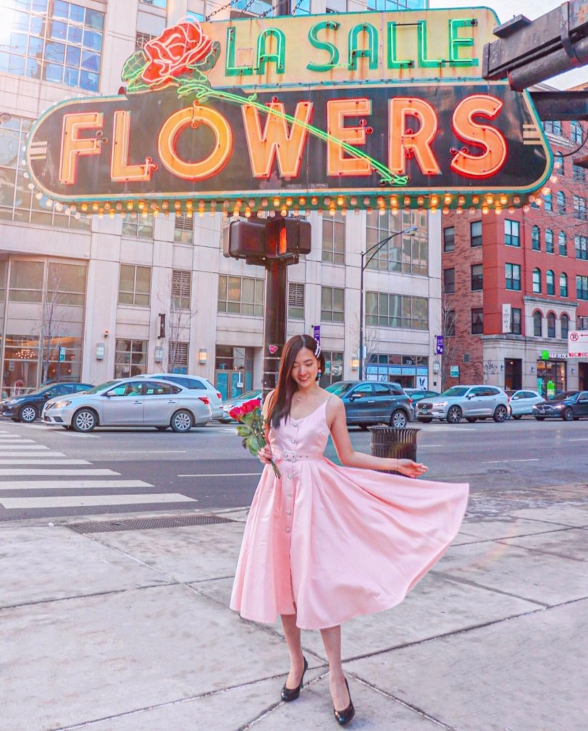 Woman in a pink dress with a flower bouquet standing in front of the Neon Sign La Salle Flowers