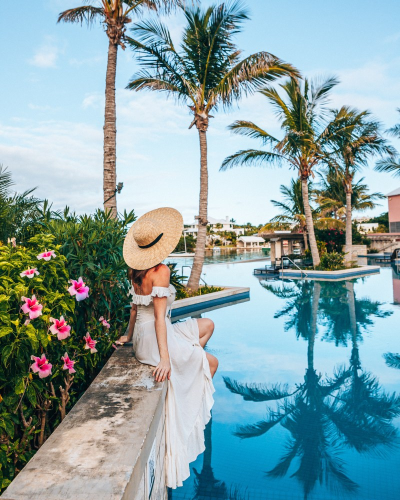Woman looking at the reflection of palm trees in the pool at Hamilton Princess Bermuda