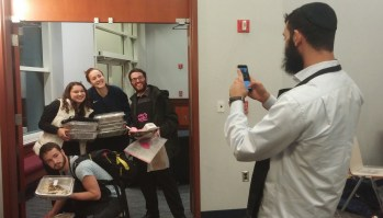Ohayon takes a picture of four students as they leave at the end of the night with their challahs ready to be baked.