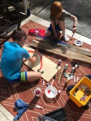 Wednesday, March 18, 2020 – Families are putting rainbows around the neighborhood for children and adults to find while social distancing. Here two children are creating their rainbows in New Orleans, LA. Bridget Falcon
