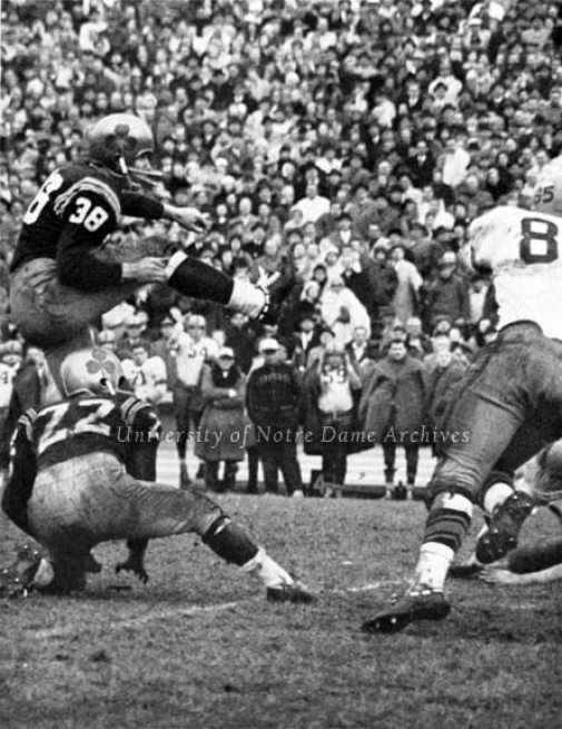 Scholastic Football Review 1961: Football Game Scene - ND vs. Syracuse, 1961/1118. Kicker Joe Perkowski (#38) kicking a second attempt field goal and George Sefcik (#22) holding the ball with no time left on the clock. Time ran out on the first kick in which Syracuse defense committed a penalty by roughing the kicker. Perkowski made the 41-yard field goal to win the game 17-15.