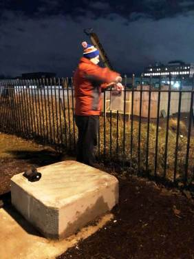 Mary Myer's installing flower and remembrance blurb, 12/17/18 [Photo: Tom Myers]