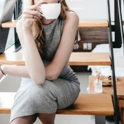 A woman sitting on the stairs in contemplation and drinking a cup of tea
