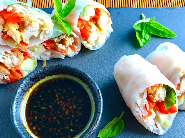 Teriyaki Chicken Summer Rolls with carrots, basil, red pepper and rice noodles inside, cut in half and stacked on slate platter with Garlic Honey Soy Dipping Sauce. Easy, fun, and delicious!