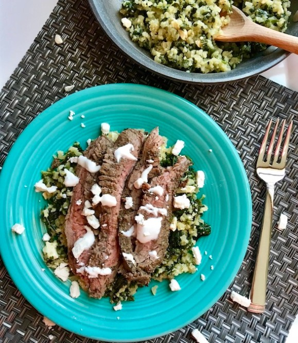 "Mediterranean Flank Steak with Kale & Feta Cauliflower Rice is a delicious Mediterranean-inspired recipe with a flavorful garlic-oregano-rubbed flank steak on top of delicious cauliflower ""rice"". To finish it off, a cool and bright Lemon & Garlic Yogurt Sauce."