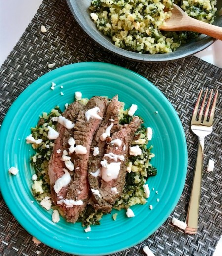 "Mediterranean Flank Steak with Kale & Feta Cauliflower Rice is a delicious Mediterranean-inspired recipe with a flavorful garlic-oregano-rubbed flank steak on top of delicious cauliflower ""rice"". Finish with a cool and bright lemon garlic yogurt sauce. The salty, texture-filled, Kale and Feta Cauliflower Rice seriously tastes just like rice filled with flavor."