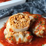 Stuffed Cabbage Rolls on a plate with one cut open. They're a great make-ahead family dish! This recipe uses ground chicken, paprika, parmesan, tomato paste, garlic, and onion for tons of flavor!