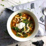 Chicken Tortilla Soup in a bowl with sour cream on top and tortilla chips on side. It's quick, it's easy, it's delicious AND...it's an all-in-one balanced dish because I have added KALE! Done in 30 minutes!