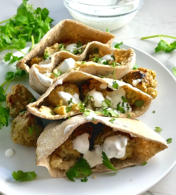 Moroccan Meatball Stuffed Pitas on a plate. They are filled with homemade hummus, moist turkey meatballs made with warm Moroccan spices like ginger, turmeric, and coriander, and then topped with creamy, fresh and bright lemon yogurt sauce.