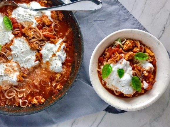 This Skillet Chicken Tomato Sauce with Ricotta is a delicious and simple one pan meal.  Ground chicken is seared until it gets a super browned, flavorful crust.  Then garlic, vegetable broth and tomatoes are added and cooked down into a delightful sauce that really lets the tomato shine with a meaty bite from the chicken.  After pasta is mixed in, creamy Ricotta Cheese is dolloped on and fresh basil added to garnish.  It's perfection! Bellissimo!