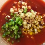 Green pepper, cucumber, garlic, scallions, red pepper, and tomato juice in a bowl for Roasted Red Pepper Gazpacho recipe from talkingmeals.com