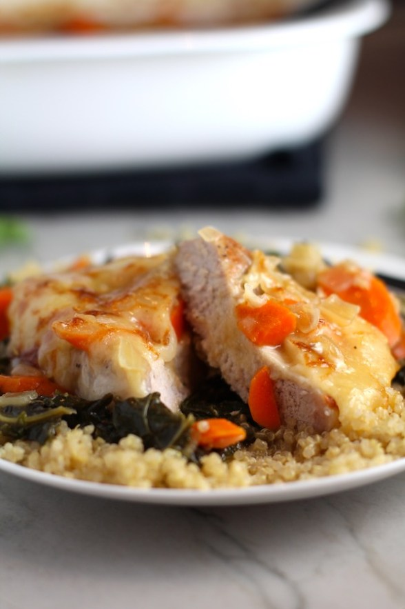 Close up of Smothered Pork Chop cut in half on quinoa with carrots and kale. This casserole is a true midwestern comfort dish with layers of vegetables and meaty pork chops smothered in a creamy sauce and cheese.  The pork chops in this delicious casserole are left whole so that you get an entire portion dripping in goodness in one scoop.