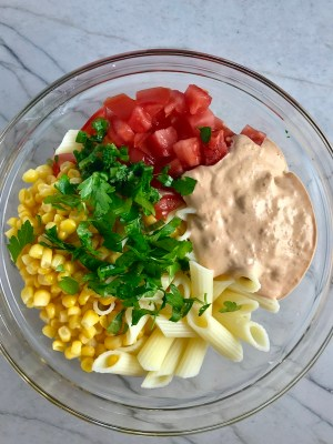 Clear bowl on counter with corn, tomatoes, pasta, Mexican dressing, and cilantro. This Creamy Mexican Pasta Salad has Sun Dried Tomatoes, Corn, Fresh Diced Tomatoes, Cilantro, and smoky Mexican spices. The dressing is creamy and smoky with lots of depth and a hint of sweetness from the Sun Dried Tomatoes that are blended in. Terrific as a side or mix in some chicken or beef and call it a meal!