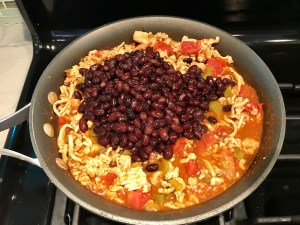 Meat, tomatoes, black beans in skillet. This Taco Casserole has corn tortillas layered with browned ground chicken seasoned with smokey mexican spices, black beans, tomatoes, and cheese, and then more cheese.