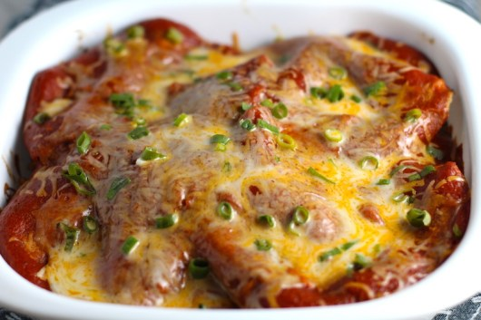 Extreme close up picture of top of taco casserole with red sauce topped with melted cheese and scallion slices. What could be better than tacos? A Taco Casserole that's made with healthier lean ground chicken and can be made ahead for your busy schedule. This Taco Casserole has corn tortillas layered with browned ground chicken seasoned with smokey mexican spices, black beans, tomatoes, and cheese, and then more cheese.