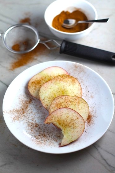 Pumpkin Spice sprinkled on apple slices fanned out on a plate with a bite taken from one slice. Recipe has 4 simple ingredients and takes minutes to make! PLUS, here are 20 EASY WAYS TO USE this Spice blend, many with no baking at all!